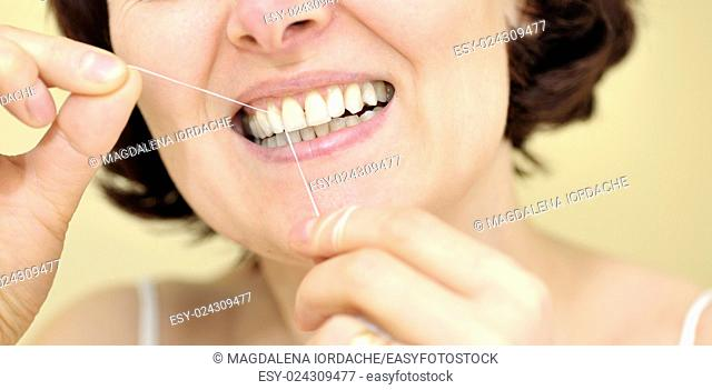 Woman flossing her teeth at home