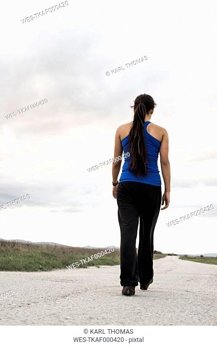 Young woman walking on an empty road by twilight, back view