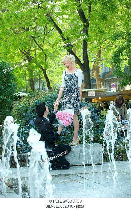 Caucasian man proposing to girlfriend near fountain