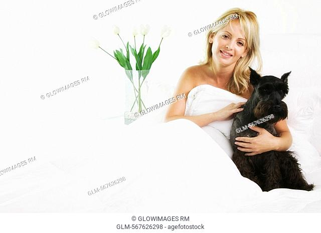 Portrait of a mid adult woman hugging her dog and smiling