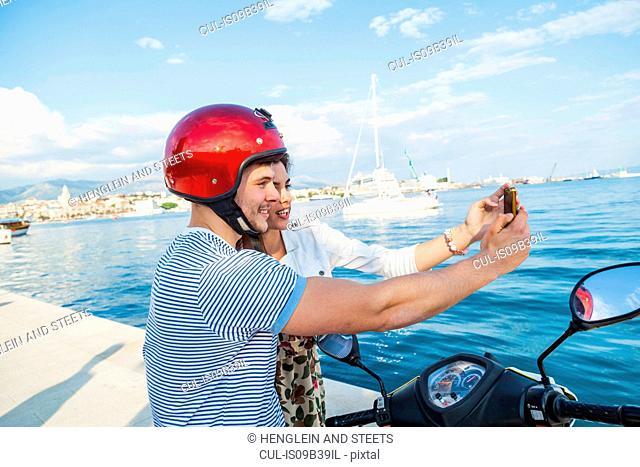 Young moped couple taking selfie at harbour, Split, Dalmatia, Croatia