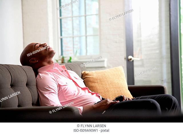 Mid adult man reclining on sofa