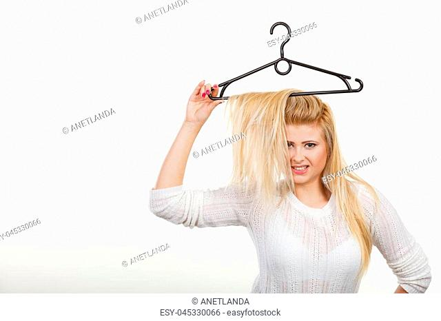 Wardrobe accessories, haircare, hair styling and selling concept. Blonde woman holding hair on clothes hanger