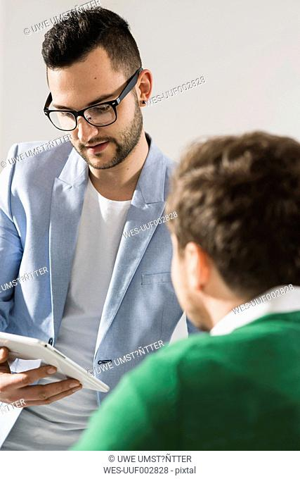 Two young businessmen with digital tablet