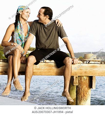 Mid adult woman with her arm around a mid adult man sitting on a jetty