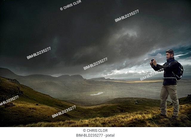 Caucasian hiker photographing storm clouds over landscape