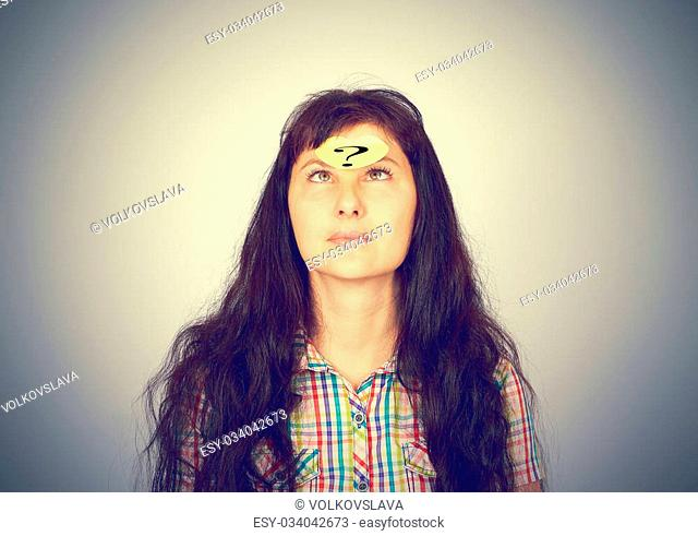 girl with a question mark over her forehead on a gray background