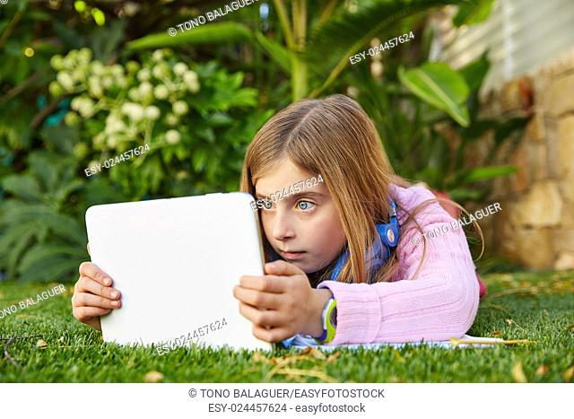 Blond kid girl with tablet pc lying on grass turf surprised expression