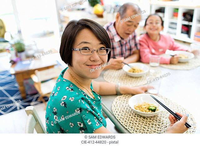 Portrait smiling woman eating noodles with family at table