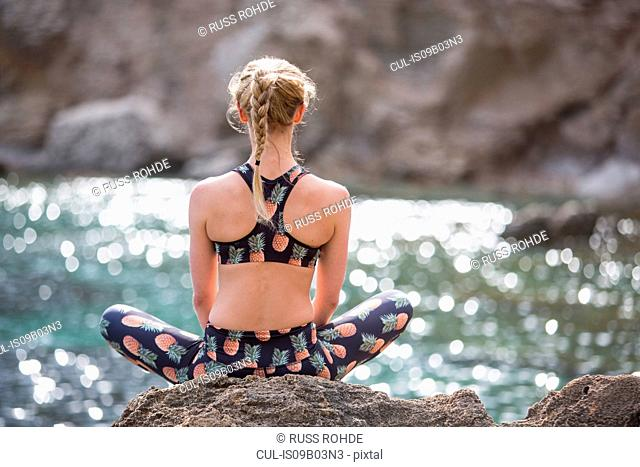 Rear view of young woman practicing yoga lotus position on sea rocks, Majorca, Spain