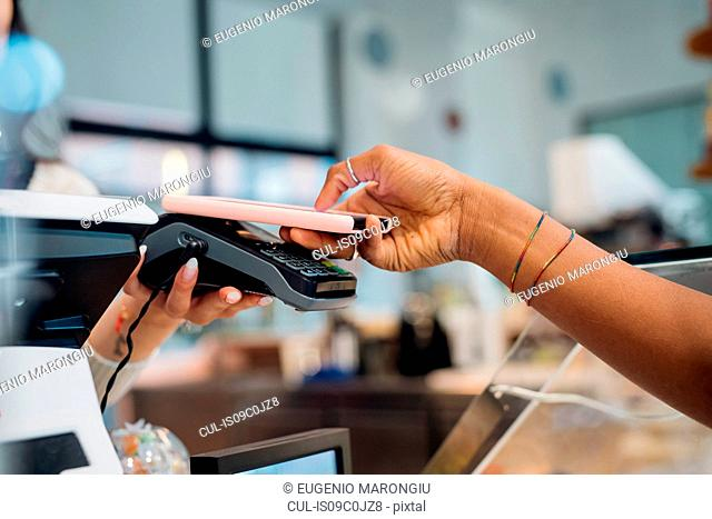 Young businesswoman making smartphone payment at cafe counter, cropped