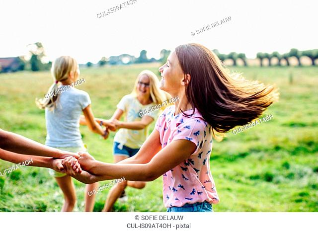 Girls dancing on field, Flanders, Belgium