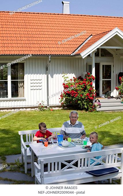Grandfather with grandsons having meal in garden