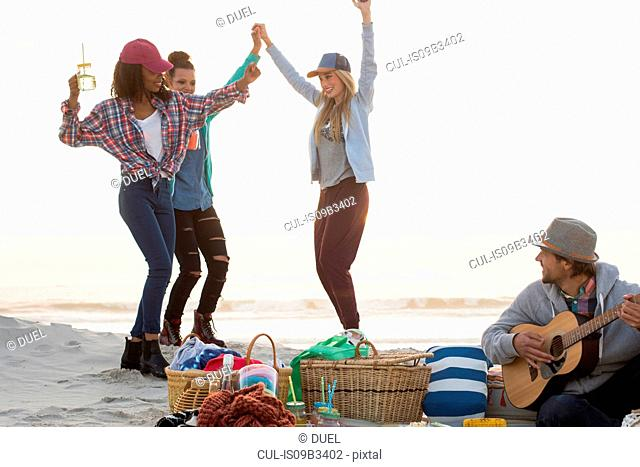 Young man playing guitar and female friends dancing at beach, Cape Town, Western Cape, South Africa