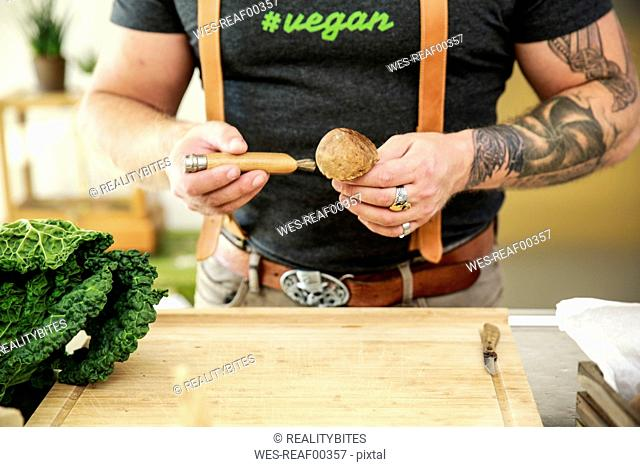 Vegan man cleaning mushrooms in his kitchen