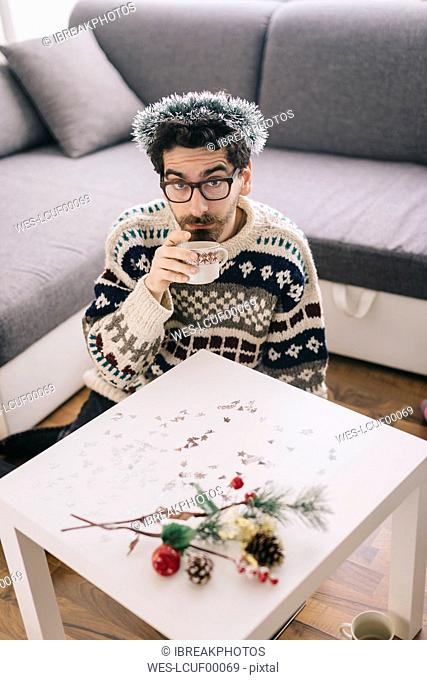 Lonely young man drinking coffee at home at Christmas time