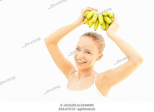 woman helds bananas on head