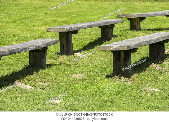 Empty wooden benches on a green meadow