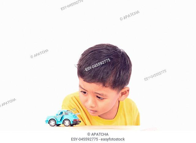 Cute asian boy play toy blur car