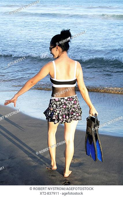 A beautiful young woman on the beach carrying fins walking towards the ocean in Mexico