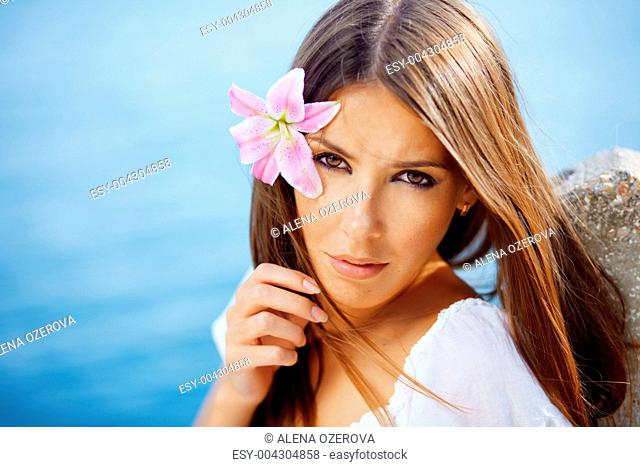 Beautiful face of woman with lily in her hair