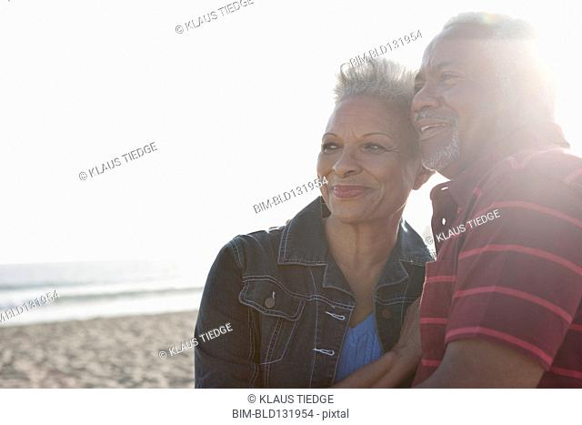 Senior African American couple hugging outdoors