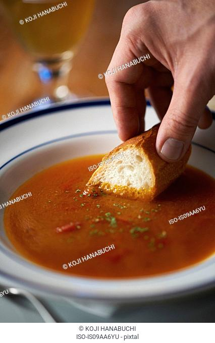 Hand dipping bread into bowl of tomato soup