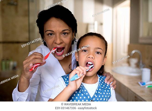 Smiling girl and grandmother brushing teeth in bathroom