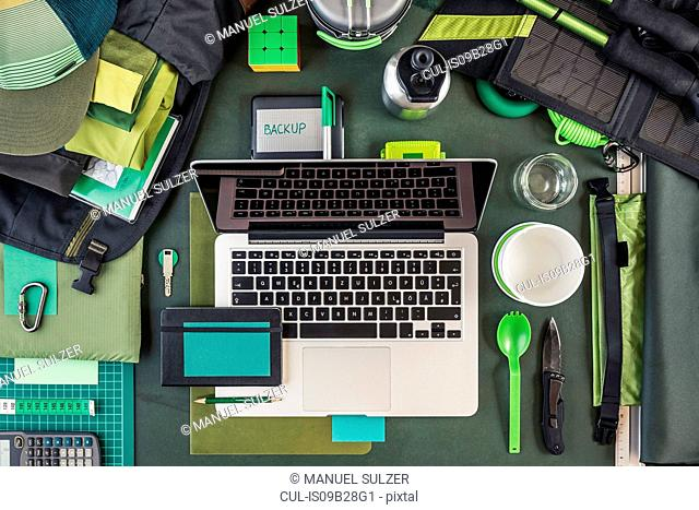 Overhead view of laptop, external hard drive and hiking equipment, green