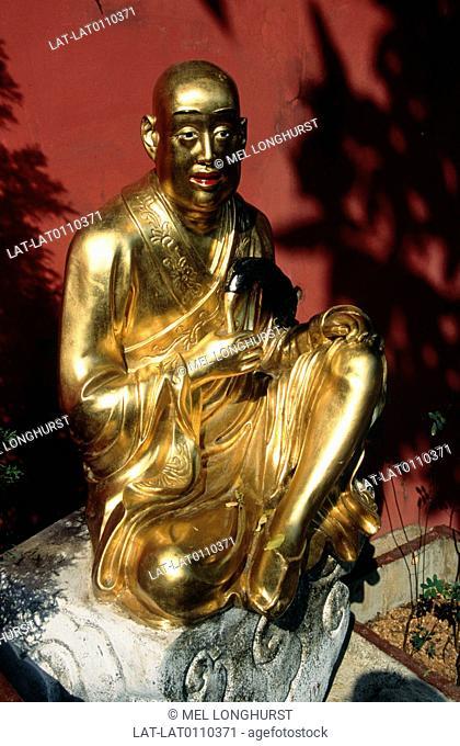 Ten Thousand Buddha monastery. Kneeling statue. Religious figures. Gold colour