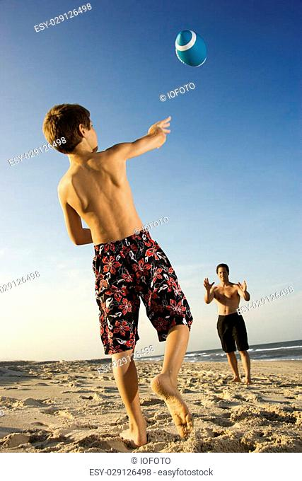 Caucasian pre-teen boy throwing football to mid-adult male
