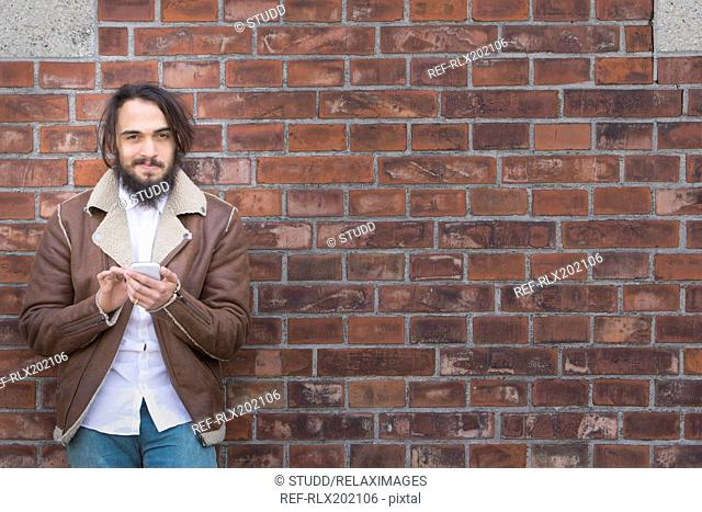 Happy young man using mobile phone against wall