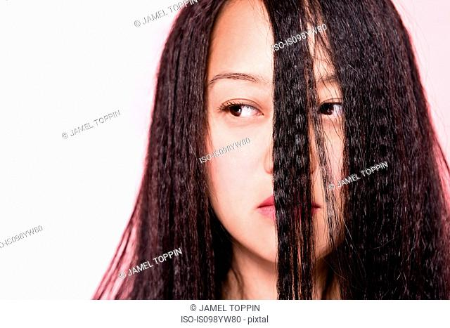 Woman with crimped hair covering face