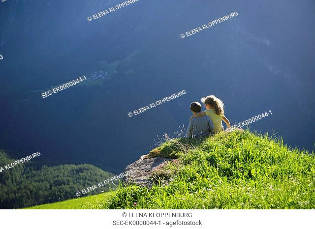 Austria, Umhausen, Girl (10-12) and boy (8-9) sitting on mountaintop