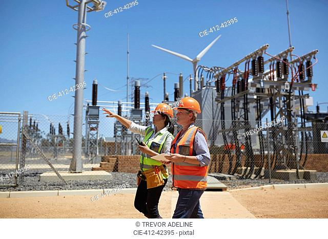 Female engineers with digital tablet at sunny power plant