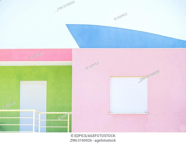 pastel colored house with closed shutter, albufeira, algarve, portugal