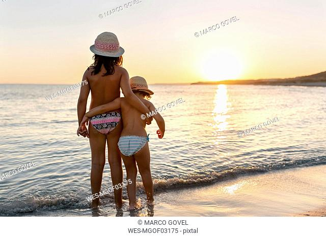 Spain, Menorca, two girls watching the sunset on the beach