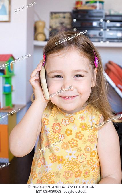 Portrait of three years old child indoors, with yellow dress, listening white smartphone mobile in her hand in ear, smiling with happy expression face