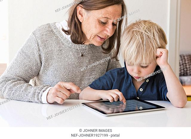 Grandmother with grandson using digital tablet