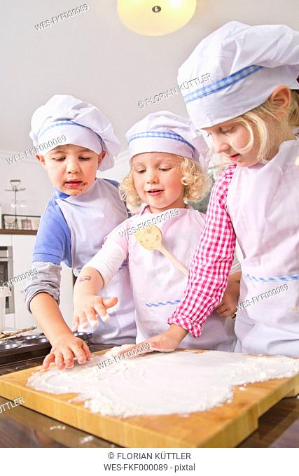 Germany, Girls and boy spreading flour for dough in kitchen