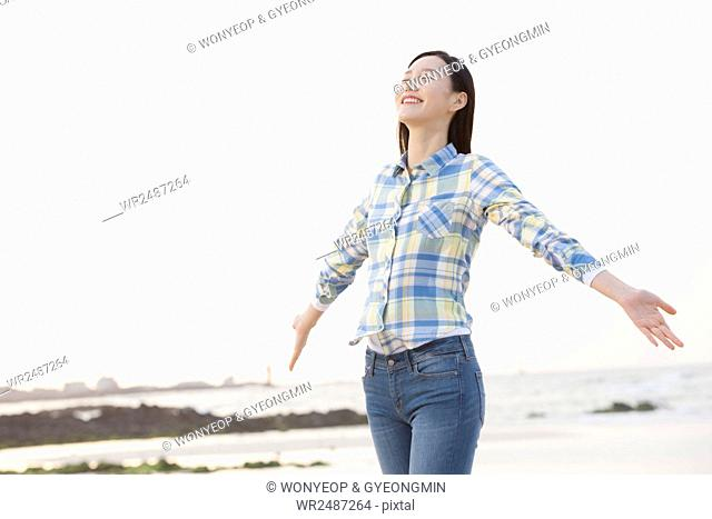 Young smiling woman standing opening arms with her eyes closed against sea