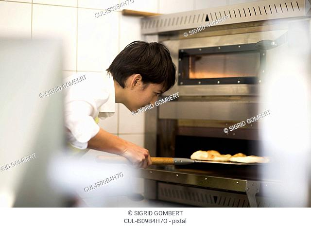 Young woman cooking food in fast food shop