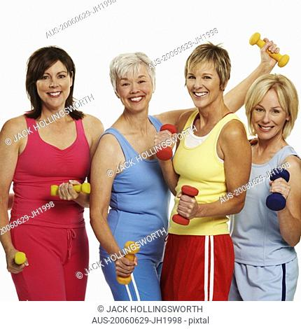 Portrait of four mature women holding dumbbells and smiling