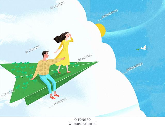 Smiling couple flying on a paper airplane in sky watching a dove