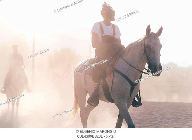 Cool young man riding horse in dusty rural equestrian arena