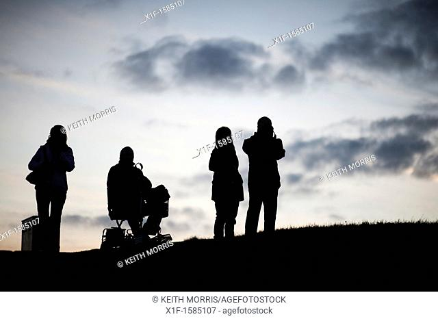 Four people, one in a wheelchair, silhouetted against the sky, Aberystwyth at dusk, October 2011
