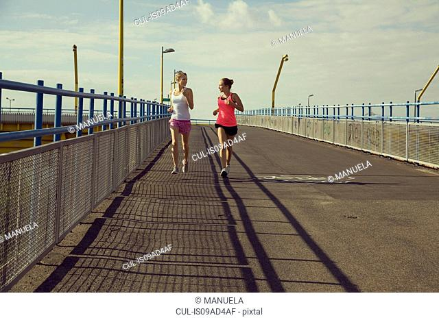 Young female joggers running on bridge