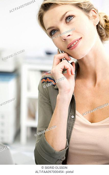 Woman talking on cell phone, head tilted