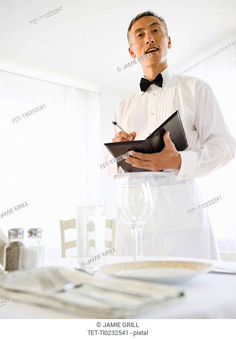 Waiter taking order and looking at camera