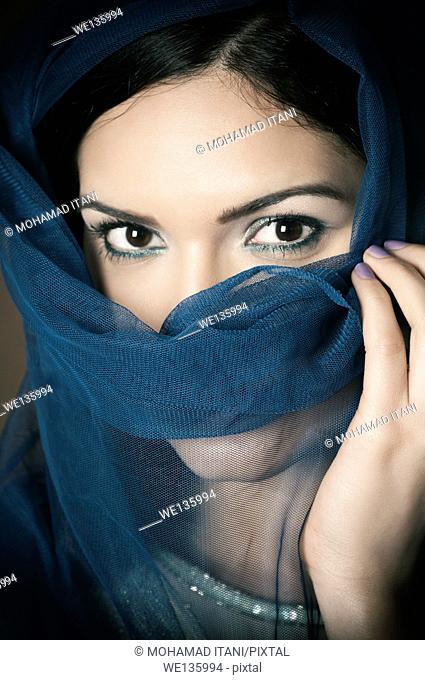 Veiled woman hiding face
